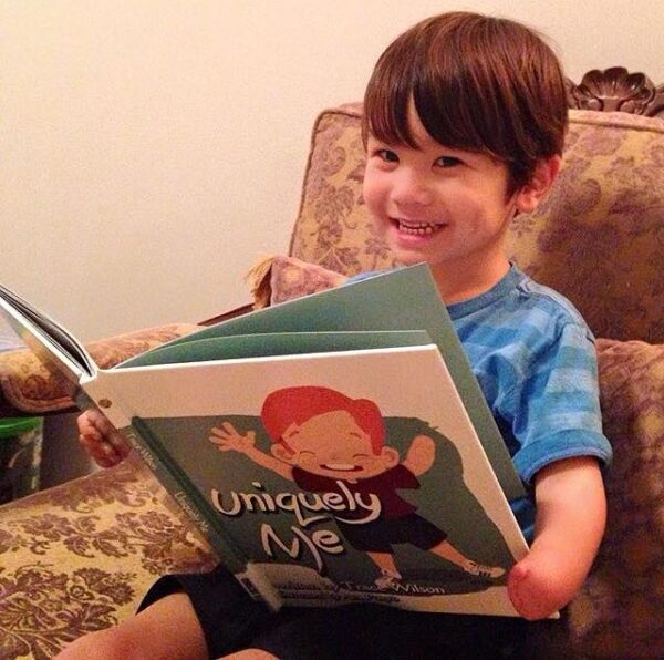 boy holding uniquely me childrens book by trace wilson