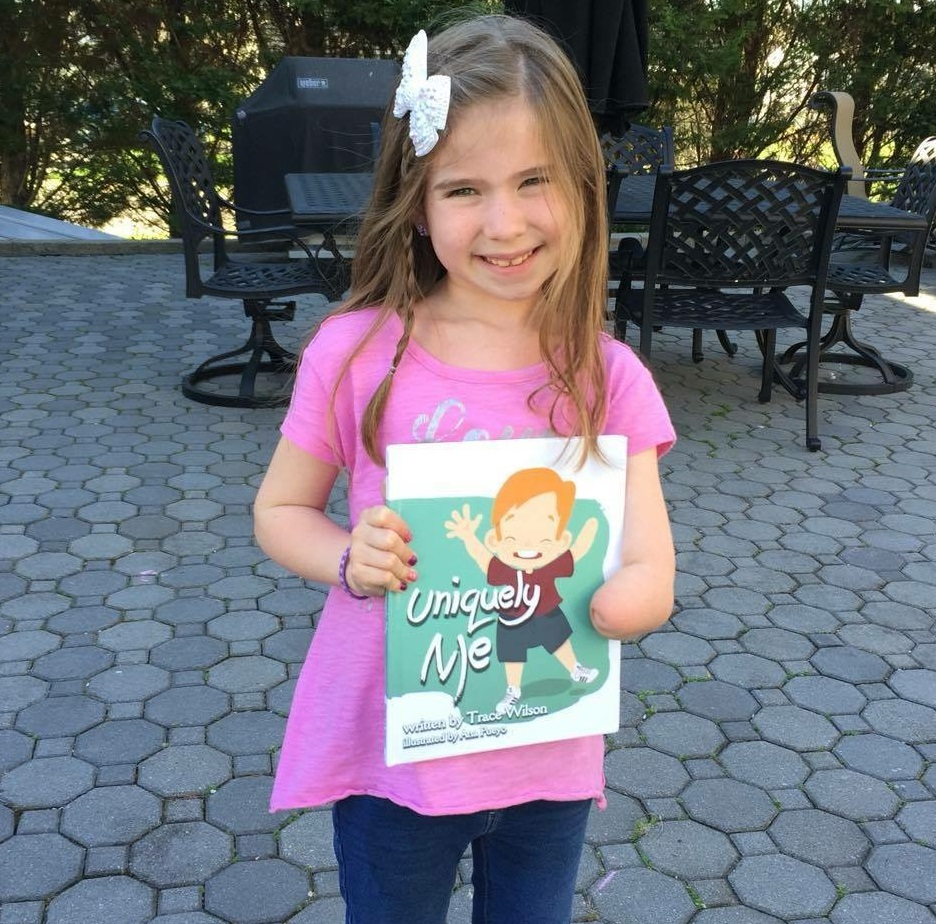girl holding uniquely me childrens book by trace wilson